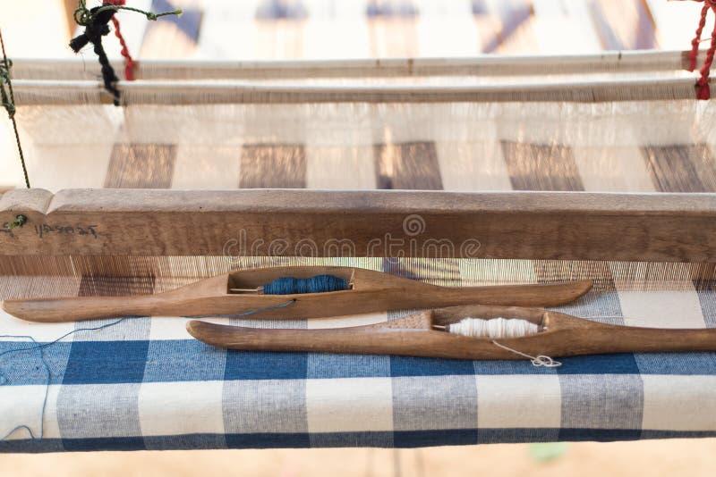 Anslutning som väver hjälpmedlet på den antika vävstolen och tråden, traditionell thailändsk väva maskin arkivbilder