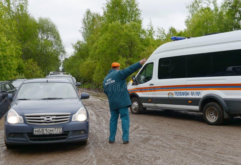 Anställd av departementet av nöd- lägen av Ryssland reglerar rörelsen av bilar på vägen nära Moskva royaltyfria foton