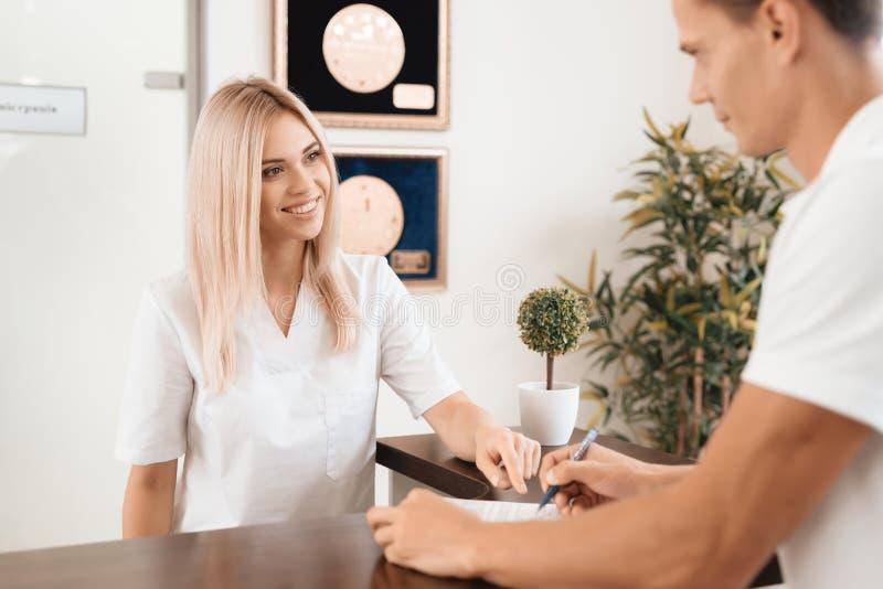 Anställd av skönhetsalongen möter klienten i mottagandet av en modern skönhetsalong royaltyfria bilder