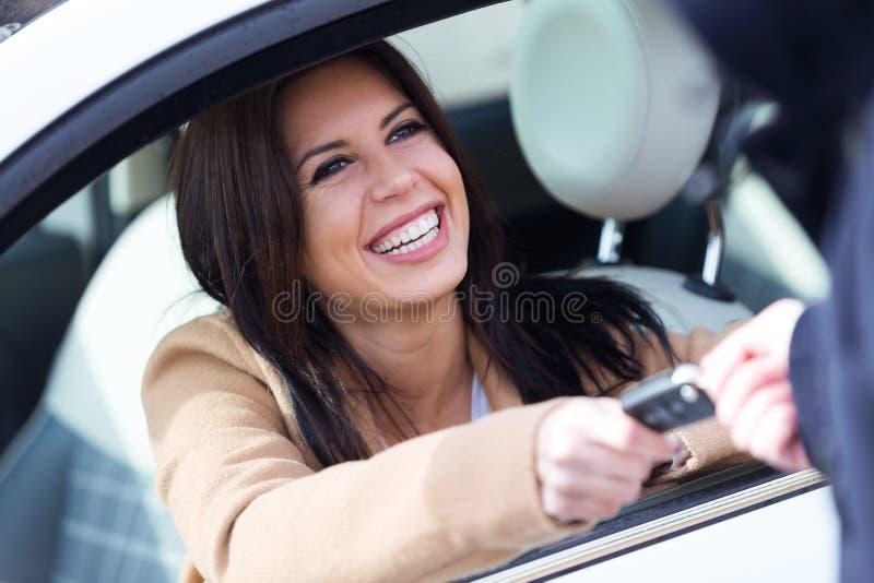 Anställd för byrå för bilhyra som ger biltangenter till den härliga unga kvinnan royaltyfri foto