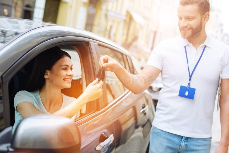 Anställd för byrå för bilhyra som ger biltangenter till kvinnan royaltyfria foton