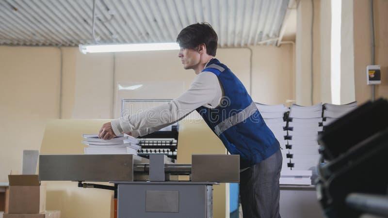 Anställd för printinghuset arbetar på printing på maskinen royaltyfri fotografi