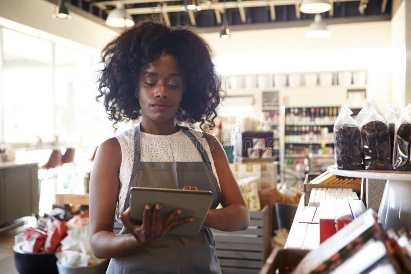 Anställd i matvaruaffär som kontrollerar materielet med den Digital minnestavlan royaltyfri fotografi