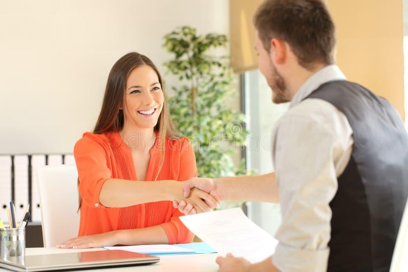 Anställd- och framstickandehandshaking efter en jobbintervju arkivbild