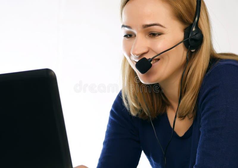 Anställd som arbetar i en appellmitt Hörlurar med mikrofontelefonförsäljningkvinna som talar på helpline arkivfoton