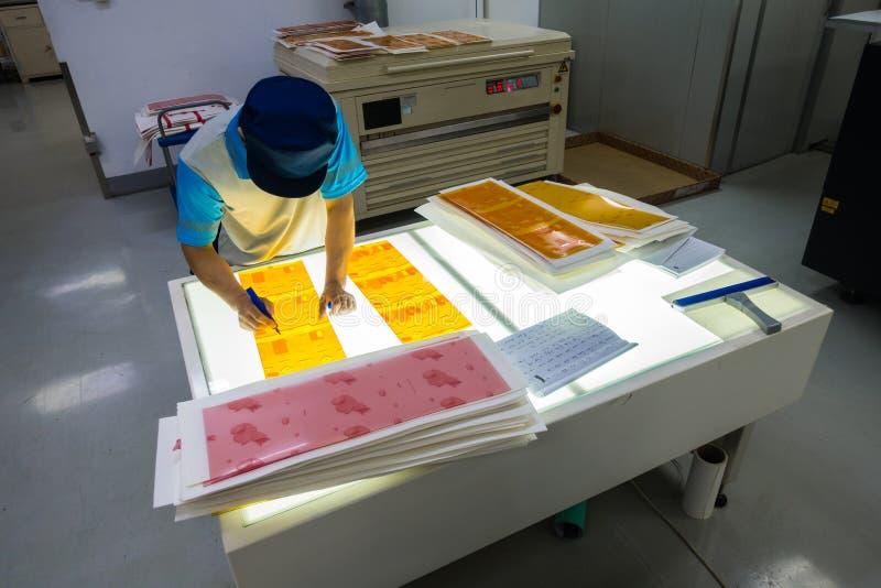 Anställd som arbetar på fabriken industriella Settin för printingutrustning arkivfoto