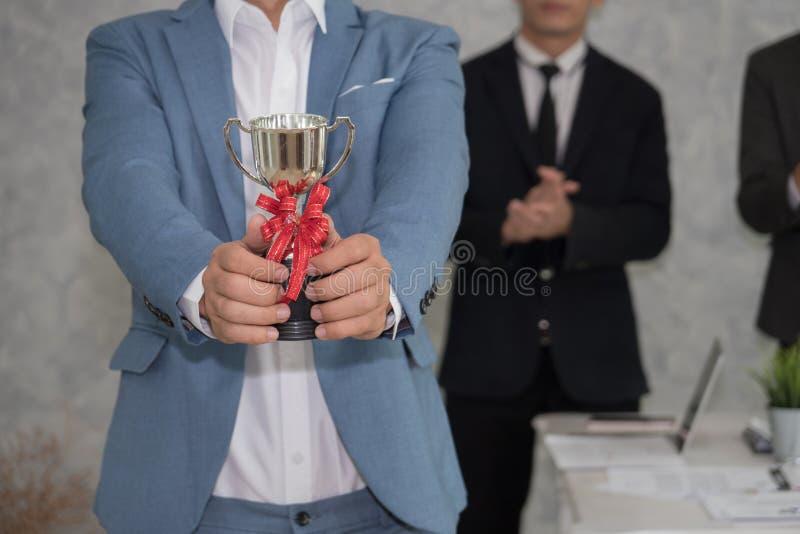 Anställd som visar troféutmärkelsen för framgång i affär royaltyfri fotografi