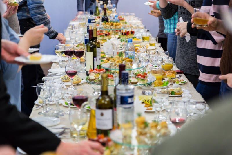 Anställda av företaget på banketten Tabell med läckerheter, alkohol och mellanmål Ett stor festmottagande arkivbilder