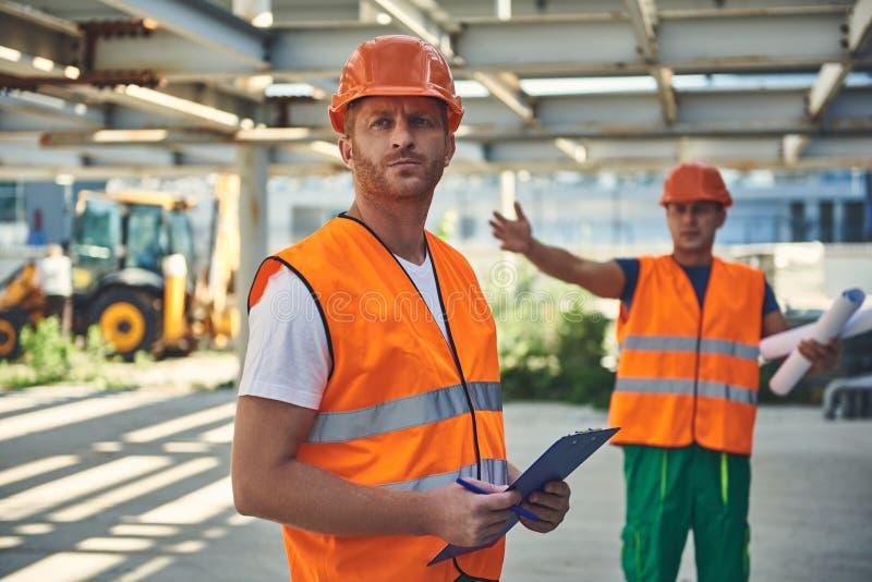 Anställda av konstruktionsföretaget på den arbetande processen royaltyfri bild