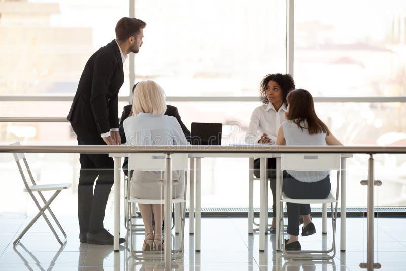 Anställda diskuterar nytt projekt med förhandsmöte för framstickandeinnehavaffären royaltyfri bild