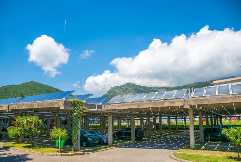 Anställda parkerade deras bilar under solpaneler på territoriet av kraftverket royaltyfria bilder