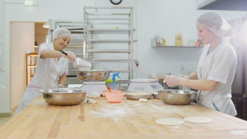 Anställda som är kvinnliga i bagerit, gör nytt bröd arkivbilder
