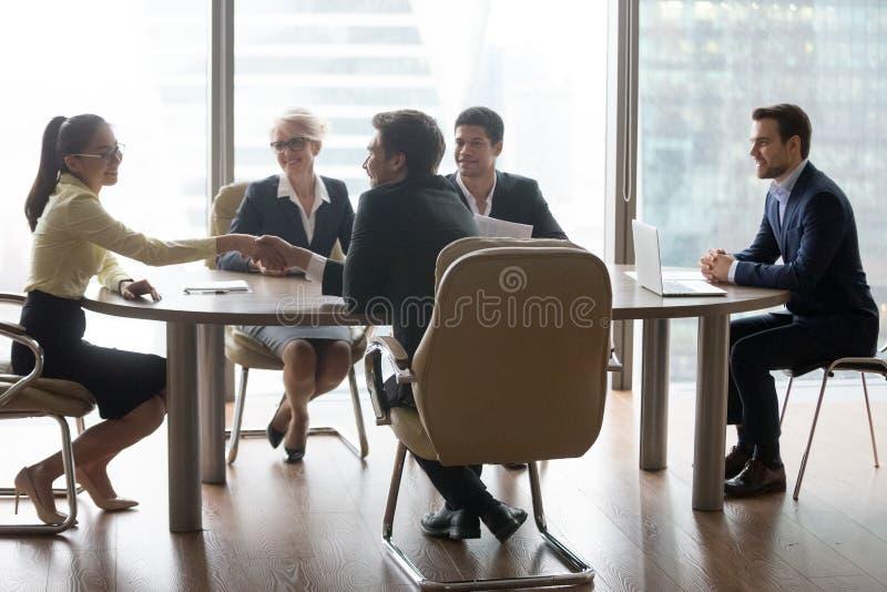 Anställda som i regeringsställning skakar händer på affärsförhandling arkivbilder