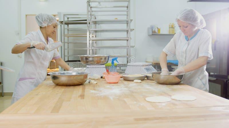 Anställdkvinnorna i bagerit gör nytt bröd royaltyfri fotografi