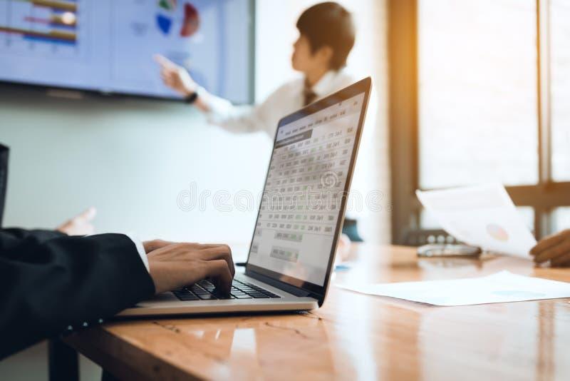 Anställdmöte som arbetar på skrivbordet och använder datorbärbara datorn på th fotografering för bildbyråer