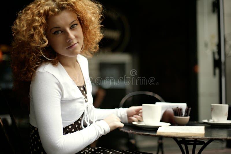 Anstarren einer jungen Frau in einem Straßenkaffee lizenzfreie stockfotos
