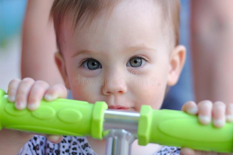 Anstarren eines lächelnden kleinen Kindes mit dem blonden Haar, das auf die grünen Griffe eines Rollers hält stockbild