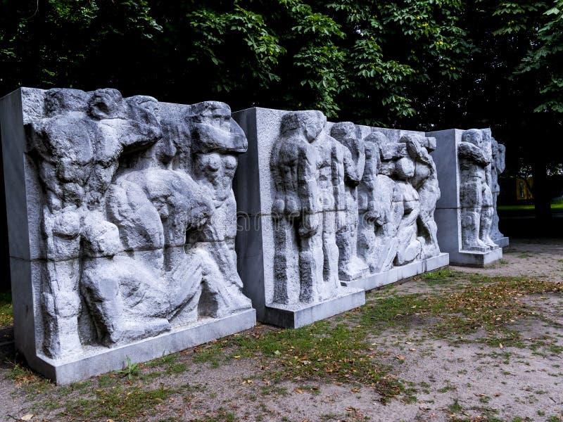 Ansträngning av den funktionsdugliga mannen på statyn av Marx och Engels i Berlin German arkivbilder