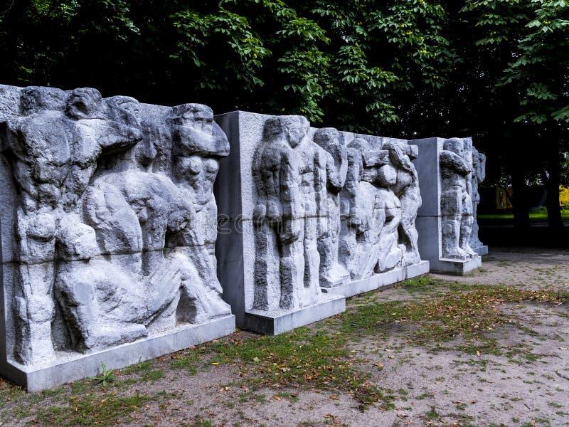 Ansträngning av den funktionsdugliga mannen på statyn av Marx och Engels i Berlin Germany arkivfoto