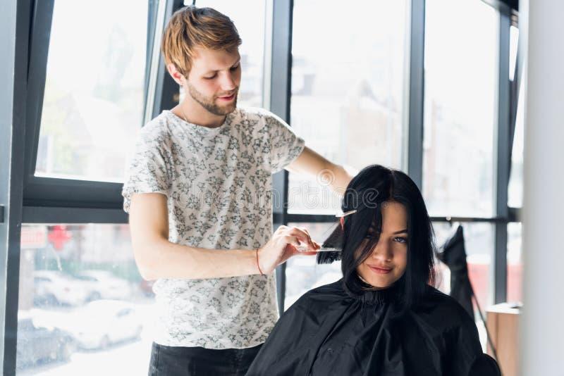 Anstreben einen Stilwechsel Junge Schönheit, die Hairstyling mit ihrem Friseur beim Sitzen in bespricht stockbild