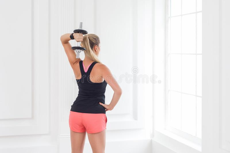 Anstreben starkes Rückseite der athletischen Bodybuilderfrau der jungen erwachsenen Motivation in den rosa kurzen Hosen und in de lizenzfreie stockfotos