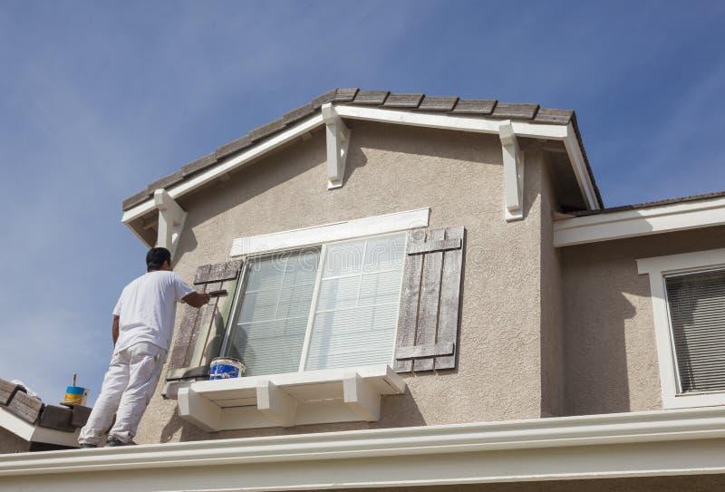 Anstreicher Painting die Ordnung und die Fensterläden des Hauses lizenzfreies stockfoto