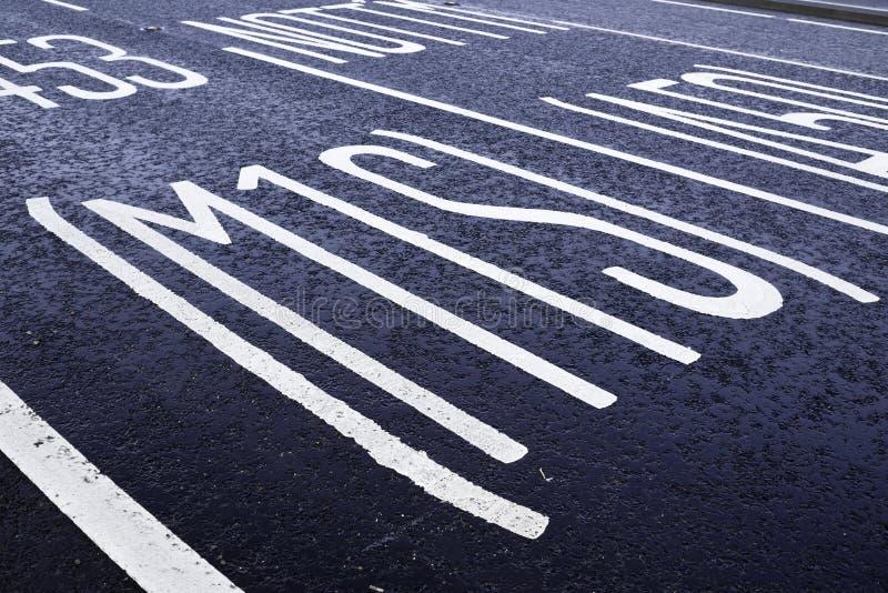 Anstrichene Straßenmarkierungen auf der Tarmac-Oberfläche stockbilder