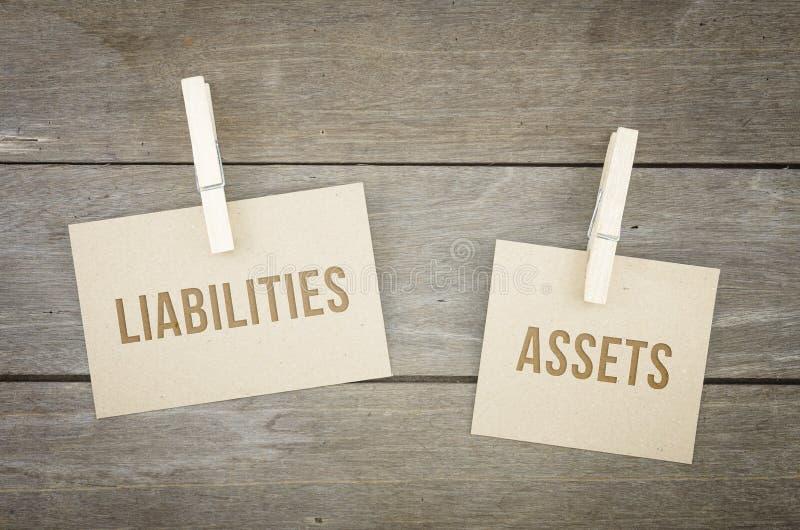 Ansvar eller tillgångar, begreppsmässiga ord för affär, träbakgrund med ark för brunt papper eller anmärkning arkivfoton