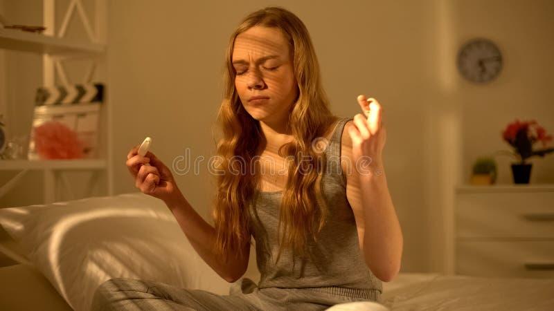 Ansvarslös tonårs- flicka som korsar fingrar och rymmer graviditetstestet, ångest royaltyfri foto