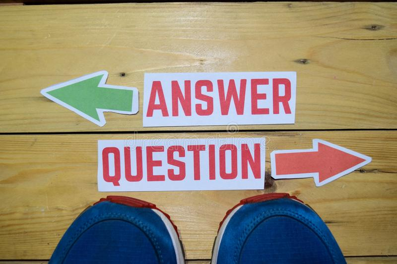 Answer or Question opposite direction signs with sneakers on wooden. Vintage background. Business, education, finance and concepts stock photo