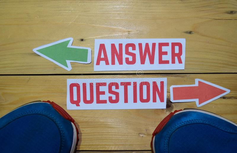 Answer or Question opposite direction signs with sneakers on wooden. Vintage background. Business, education, finance and concepts stock images