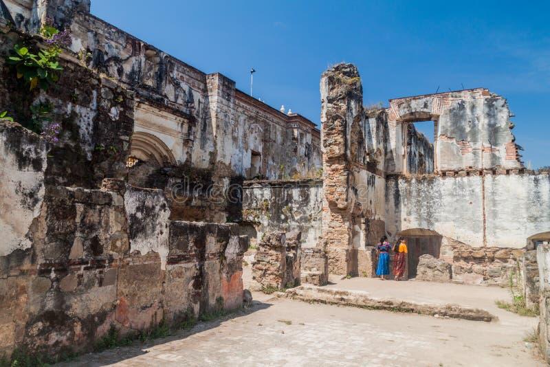 ANTÍGUA, GUATEMALA - 27 DE MARÇO DE 2016: Duas fêmeas locais visitam ruínas da catedral do Santiago em Antígua Guatema imagem de stock royalty free