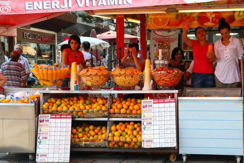 ANTALYA, ΤΟΥΡΚΙΑ - 27 Ιουλίου 2012, όμορφοι πωλητές κοριτσιών των καταστημάτων που πωλούν τους φρέσκους νεύοντας πελάτες χυμού, σ στοκ φωτογραφία με δικαίωμα ελεύθερης χρήσης