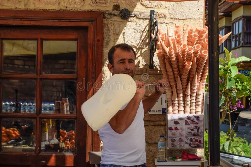 The ice cream seller is spinning ice cream on a stick stock photography