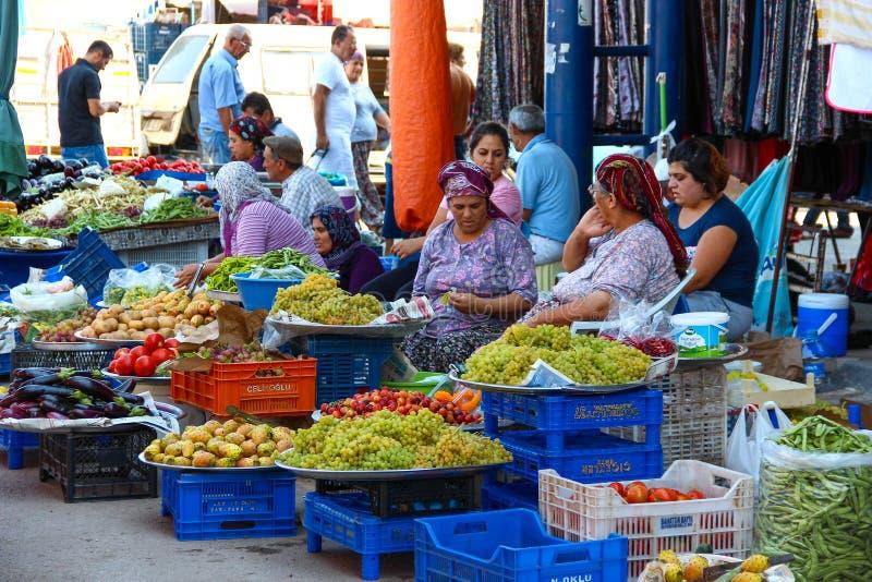 ANTALYA, TURKIET - Augusti 14 2012, sikt av traditionella marknader för en gata, var gammalt och unga kvinnor som säljer frukt oc royaltyfria bilder
