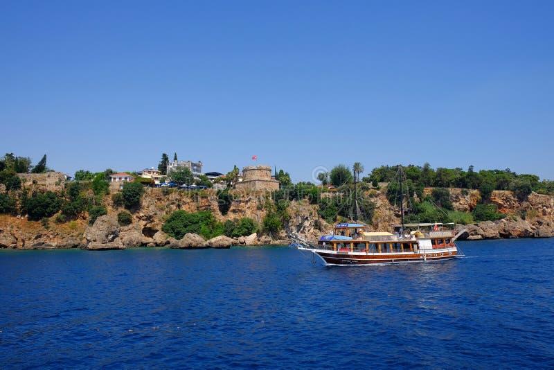ANTALYA, TURKIJE - JULI 0€4€¬ 2019: Weergeven op de Hıdırlık-Toren en een toeristische boot in Antalya royalty-vrije stock afbeelding