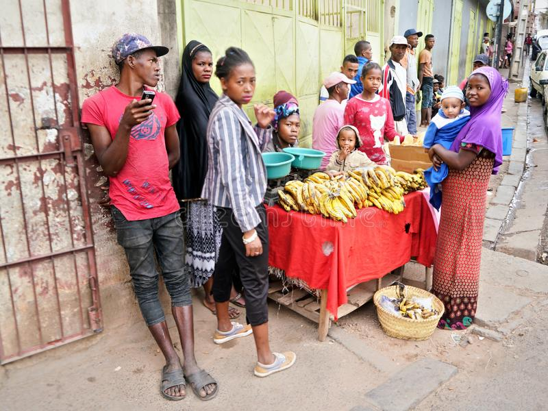 Antananarivo, Madagascar - April 24, 2019: Group of unknown Malagasy people standing near woman selling bananas on the street. royalty free stock image