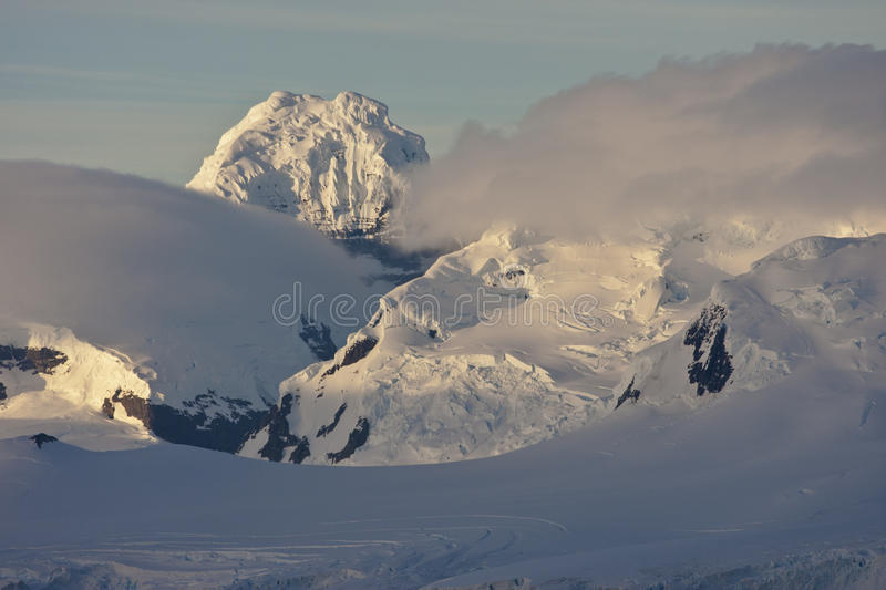 Antarctic Peninsula in the first morning light. Fog layers around the mountains on the Antarctic Peninsula in the first morning light royalty free stock photography