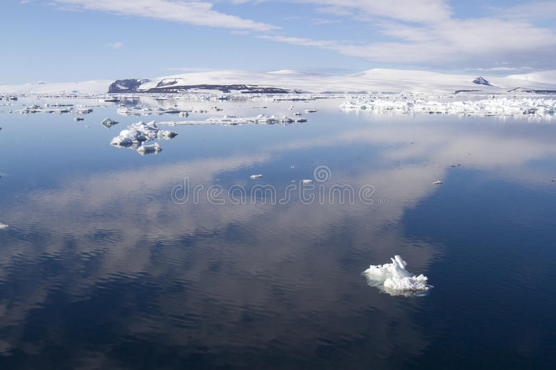 Antarctic Sound reflecting clouds in calm waters. Reflection of cloudscape in calm waters of Antarctic Sound on sunny day with floating ice stock photography