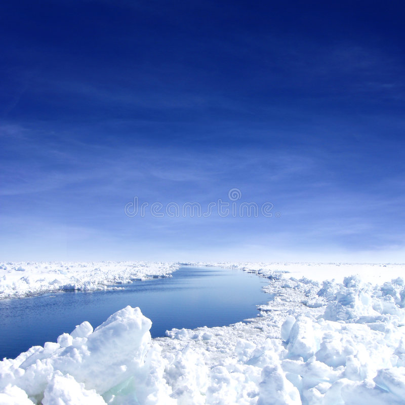 Antarctica. Ice field with snow and ice, channel of blue water through it, dark blue sky royalty free stock photos