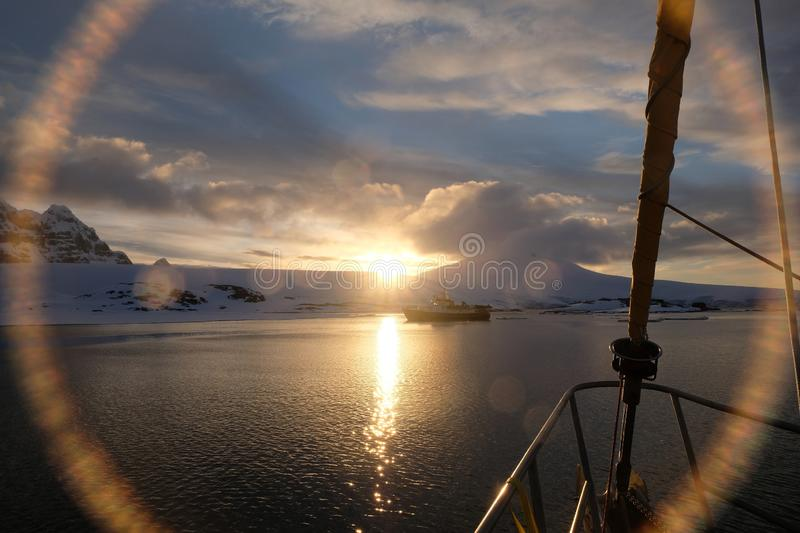 Antarctica calm midnight sunset lens flare from sailboat stock photography