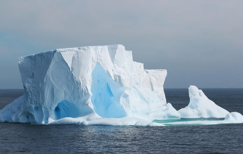 Antarctica on a Cloudy day- Antarctic Peninsula - Huge Icebergs and gray sky. Blue Ice royalty free stock photo