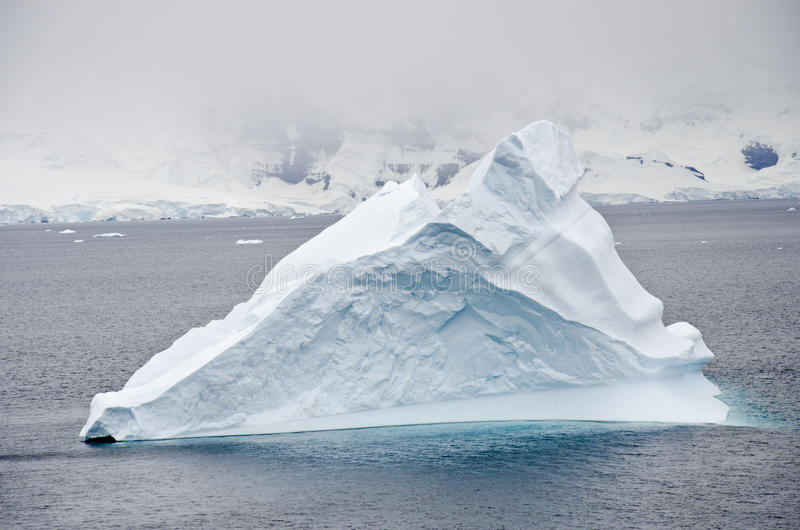 Antarctica - Non-Tabular Iceberg Drifting In The Ocean. Antarctica In A Cloudy Day - Global Warming stock photo