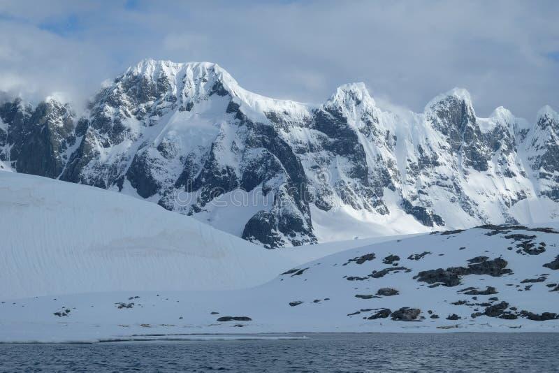 Antarctica szczerbił śnieżne góry w ranku świetle na chmurnym dniu obraz stock