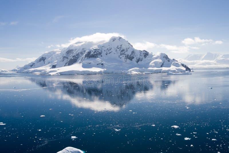 Antarctische ijs-behandelde berg die in water wordt weerspiegeld stock afbeelding
