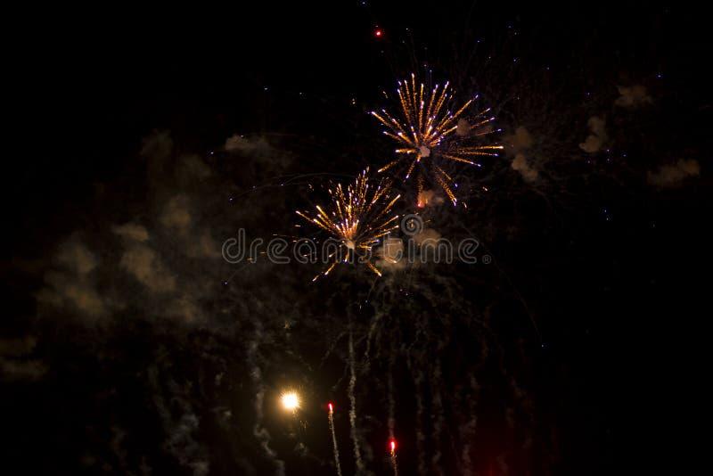 Antecedentes abstractos: Subiendo y estallando los fuegos artificiales anaranjados y púrpuras con humo imagen de archivo