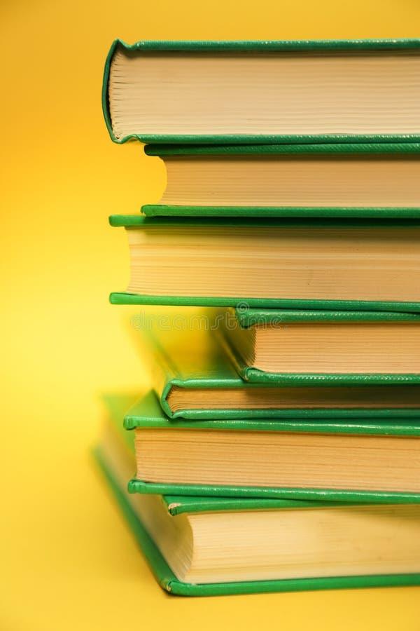 Antecedentes amarillos y un montón de libros, estudiando libros de texto imagen de archivo libre de regalías