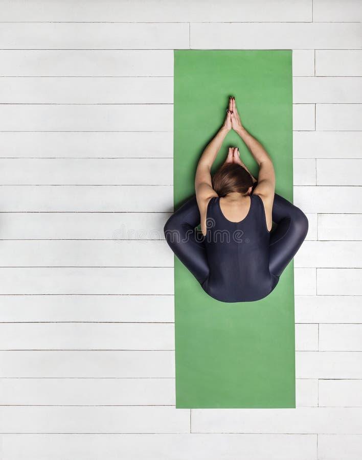Antecedentes: práctica de la yoga en la alfombra verde y la Florida de madera blanca foto de archivo