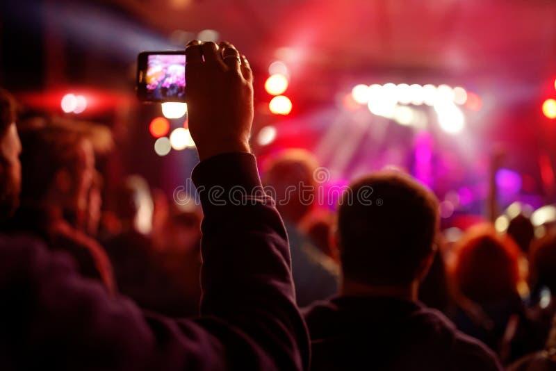 Anteckna videoen med smartphonen under en konsertsommarmusik f royaltyfria foton