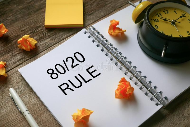 Anteckningar, papperskassett, klotpenna och anteckningsbok med 80/20 Regel på träbakgrund royaltyfria bilder